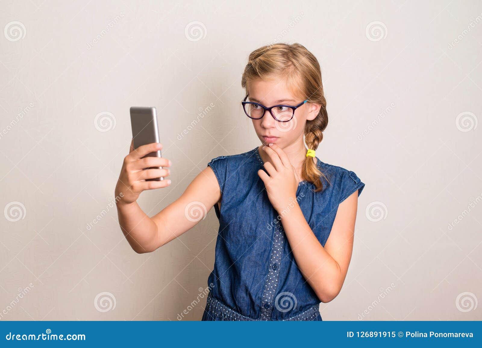 Ragazza teenager abbastanza sorridente in vetri che fanno la foto del selfie su astuto