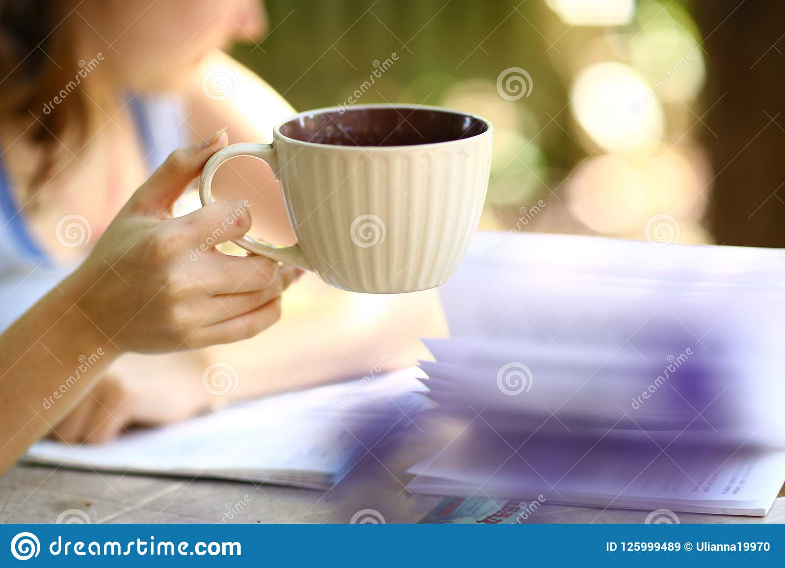Ragazza teenager con la fine della tazza di tè della tenuta del libro sulla foto