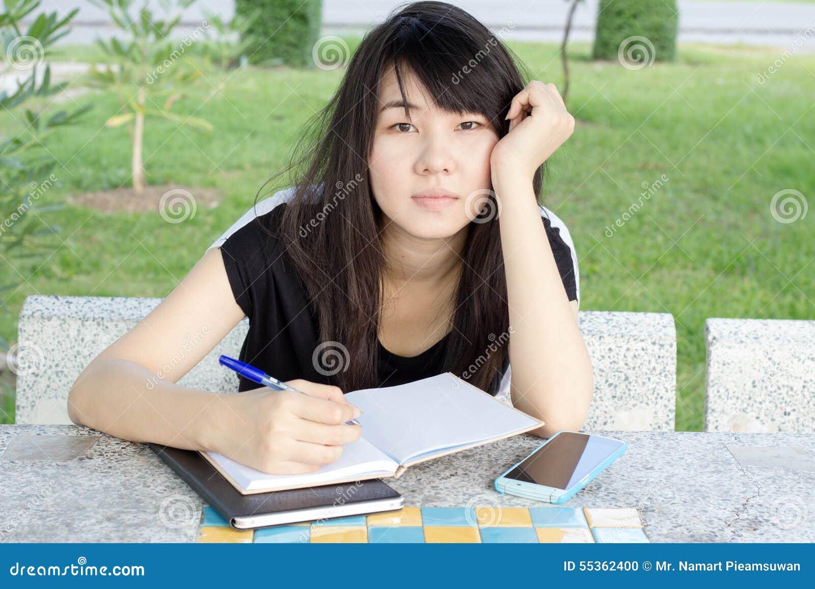 Ragazza teenager dello studente tailandese la bella scrive un libro che si siede in parco