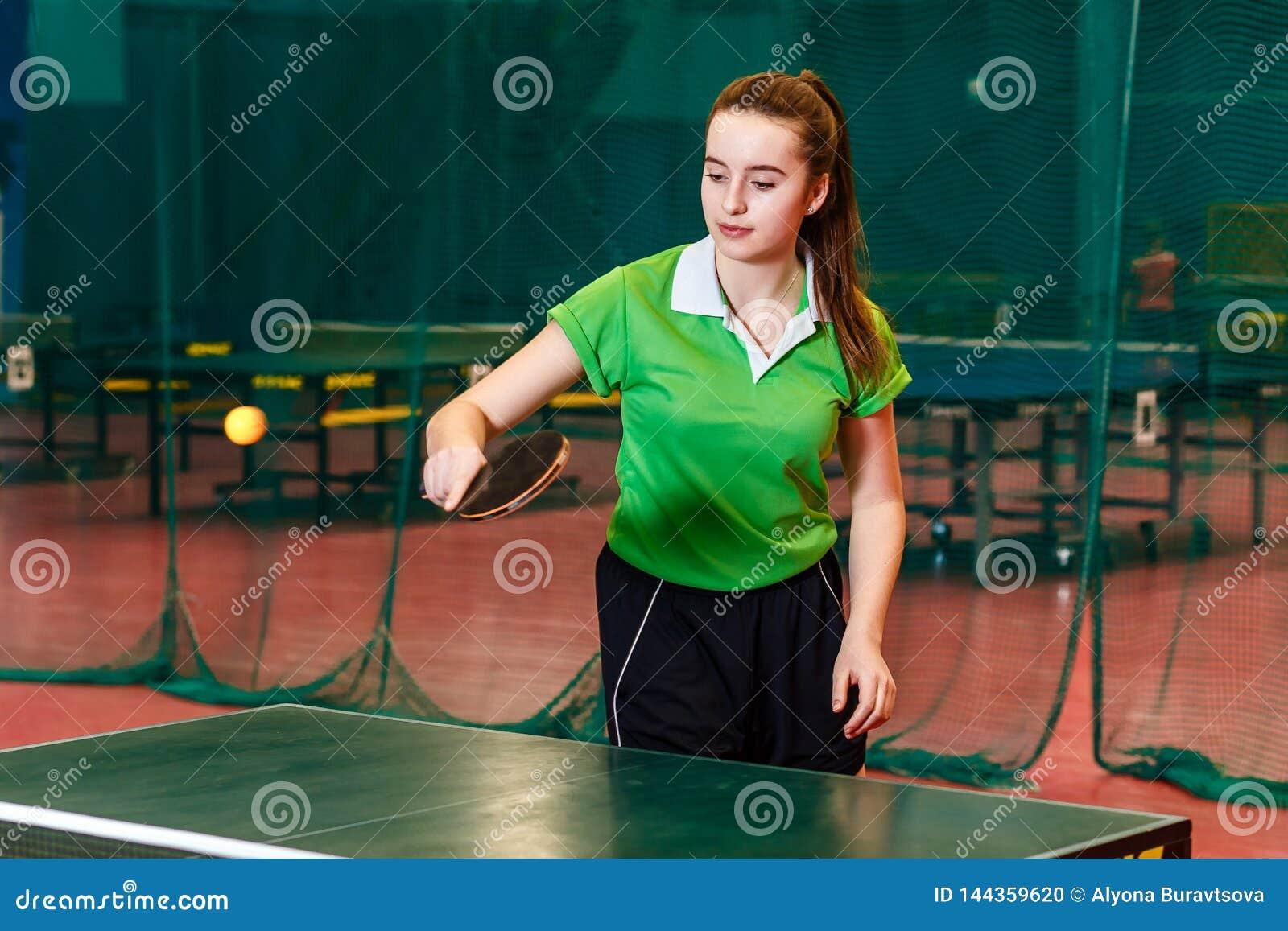 Ragazza teenager di quindici anni in maglietta verde di sport che gioca ping-pong