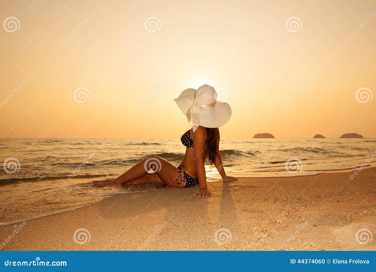 Ragazza in un cappello di paglia su una spiaggia tropicale al tramonto Estate