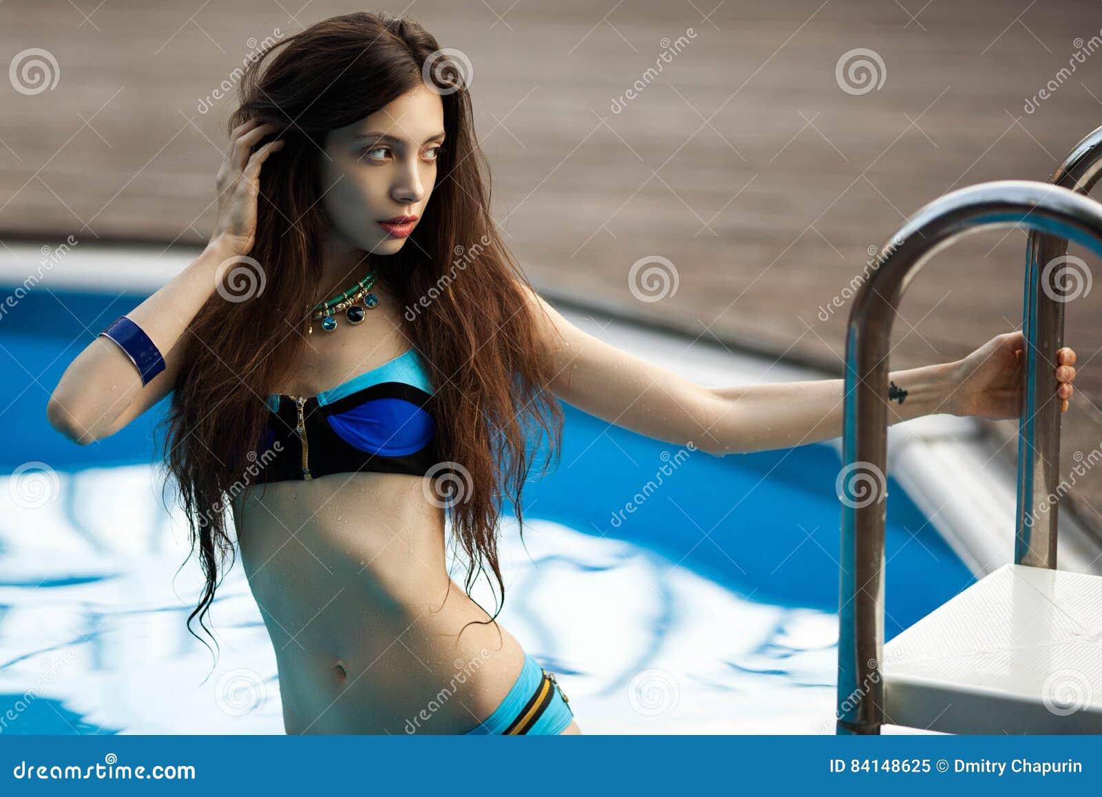 Ragazza in un costume da bagno sui precedenti dello stagno