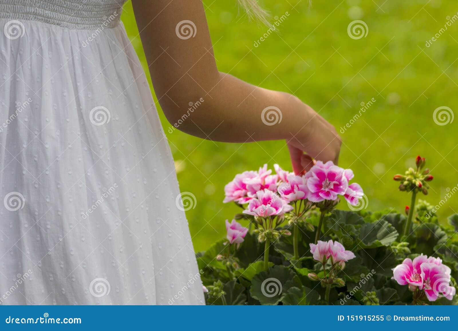 Ragazza in un vestito che seleziona i fiori