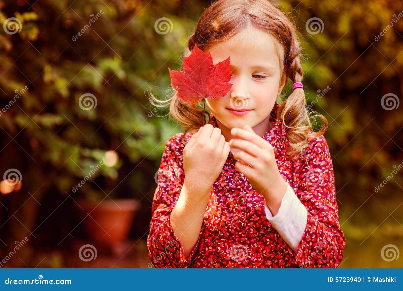 Ragazza vaga sveglia del bambino che si nasconde dietro la foglia rossa di autunno nel giardino