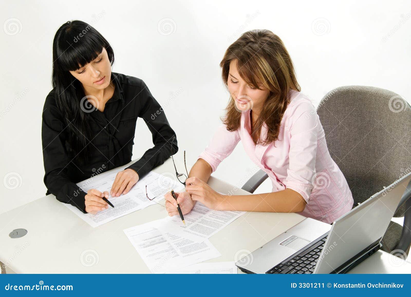 Ragazze con il computer portatile ed il documento