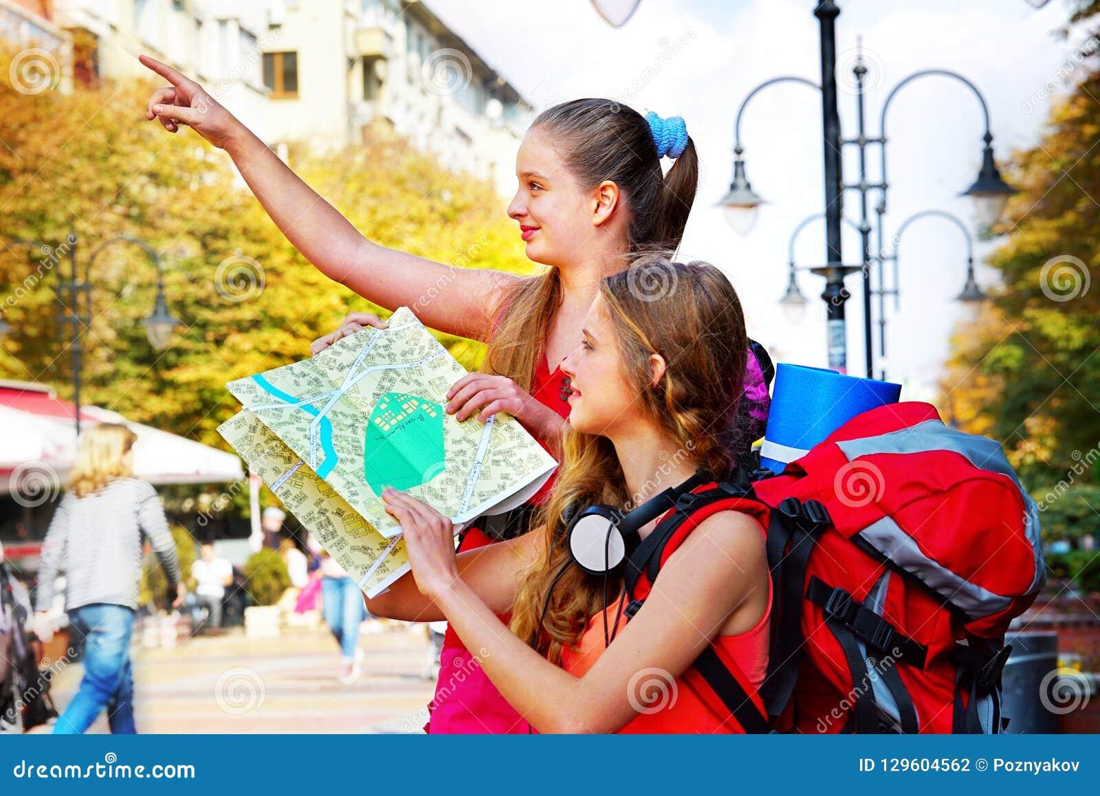 Ragazze del viaggiatore con lo zaino che cerca la mappa di carta turistica di modo