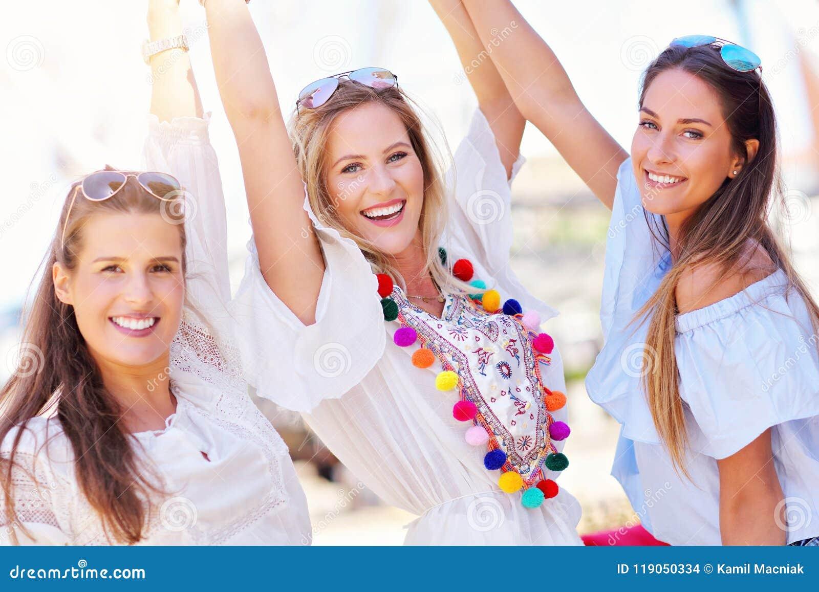 Ragazze felici che vanno in giro nella città di estate