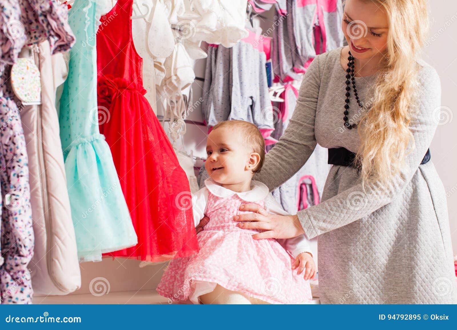 47d406d6038c Bella bambina sveglia con il suo vestito da acquisto della madre in negozio