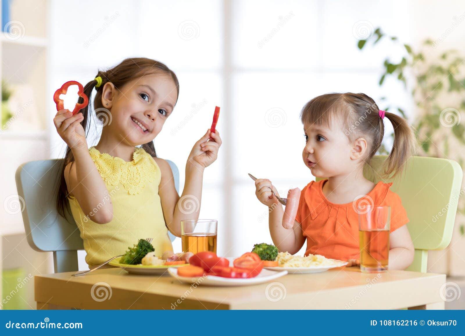 Ragazze sveglie dei bambini che mangiano alimento sano Pranzo dei bambini a casa o asilo
