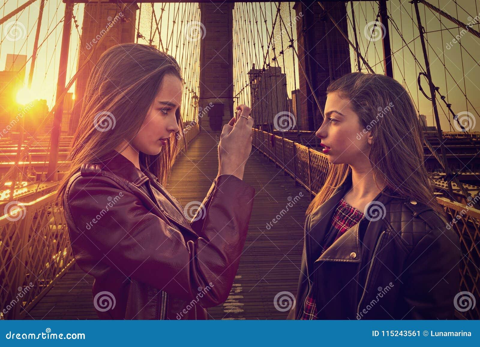 Ragazze turistiche teenager che prendono foto in ponte di Brooklyn NY