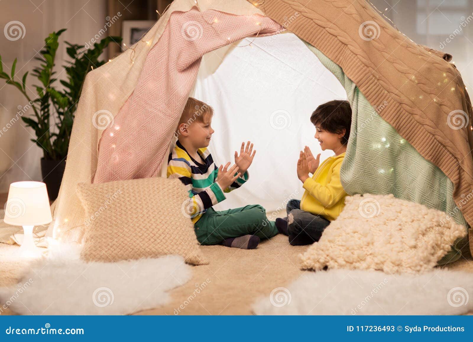 Ragazzi che giocano gioco dapplauso in tenda dei bambini a casa