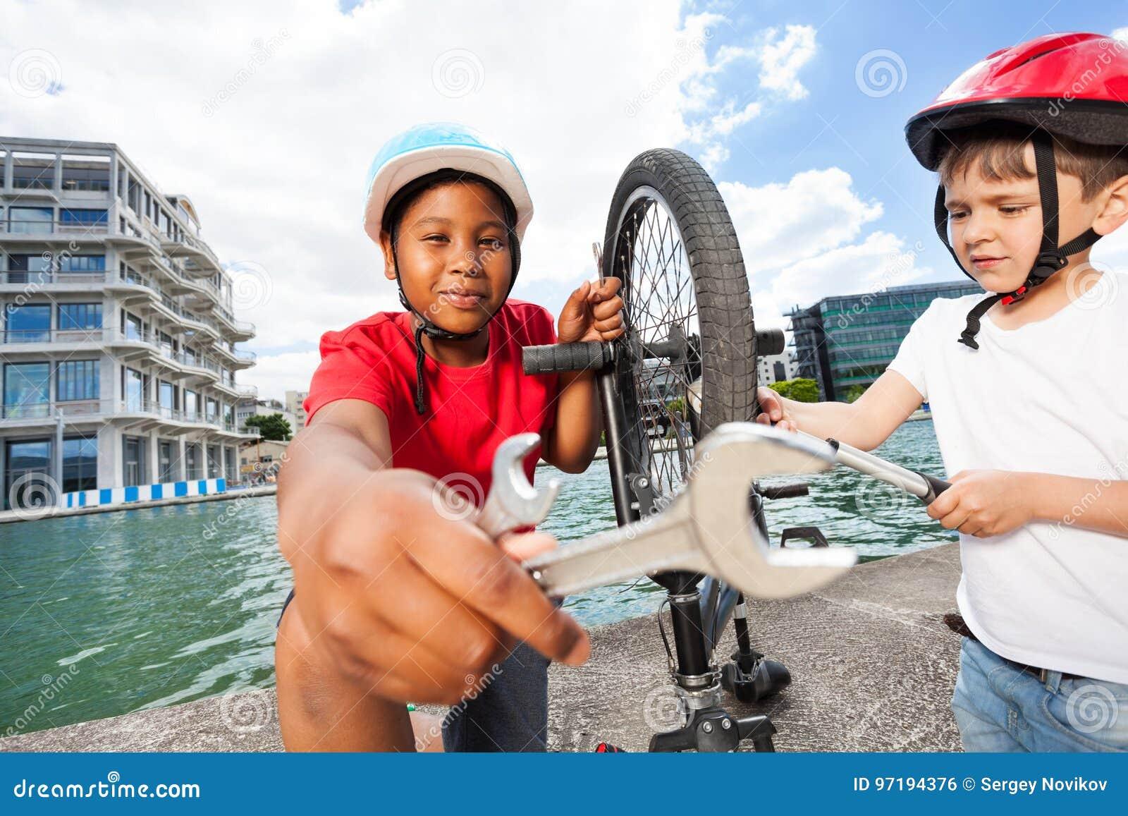 Ragazzi felici che riparano insieme bici all aperto di estate