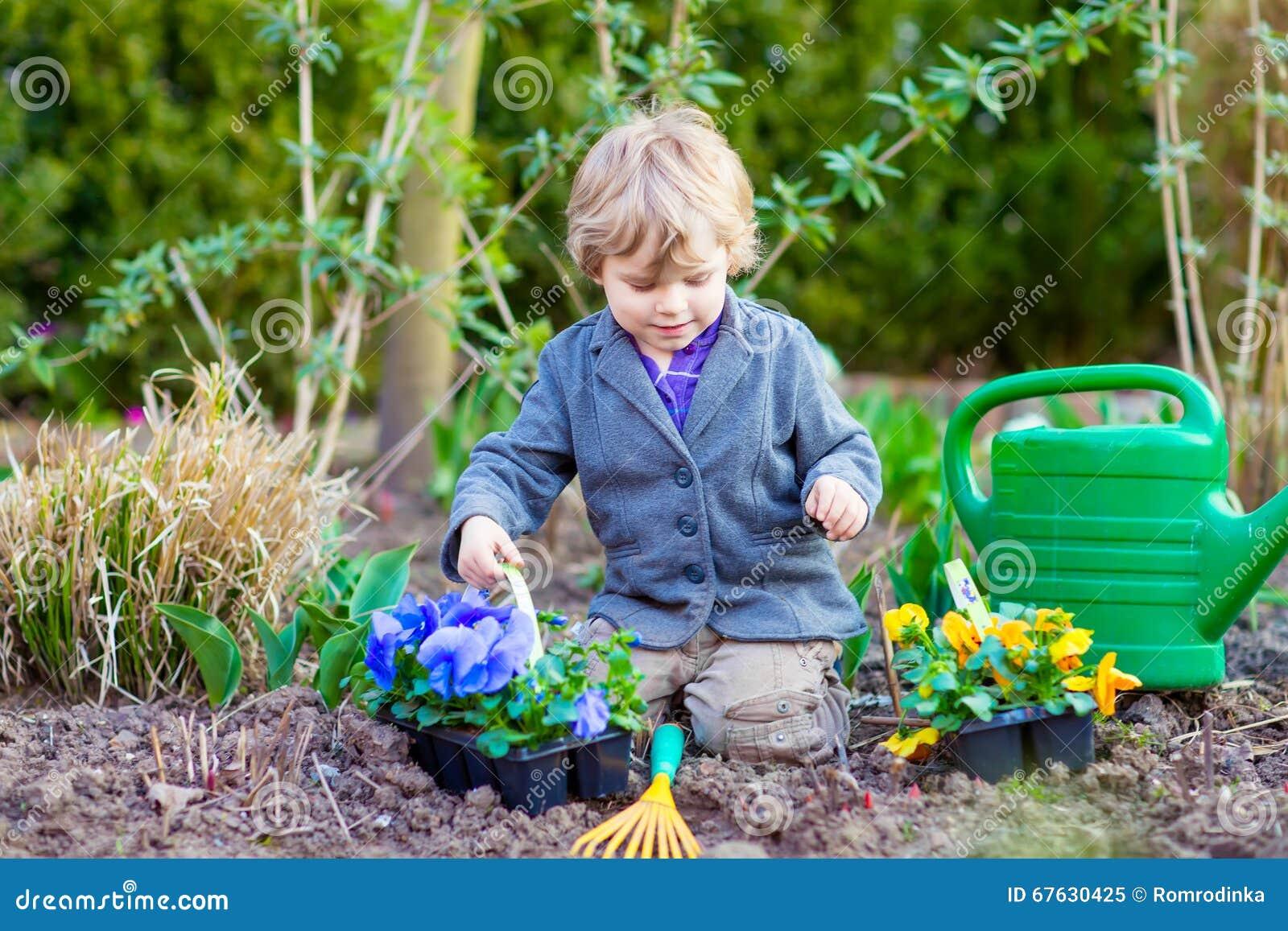 Ragazzino che fa il giardinaggio e che pianta i fiori in for Giardinaggio e fiori
