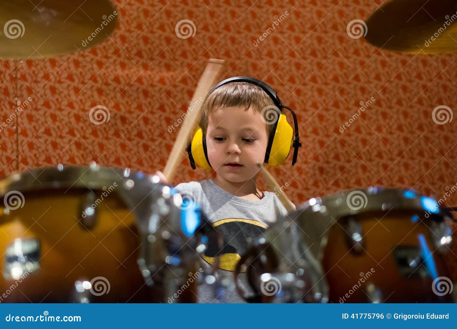 Ragazzino che gioca i tamburi con le cuffie di protezione