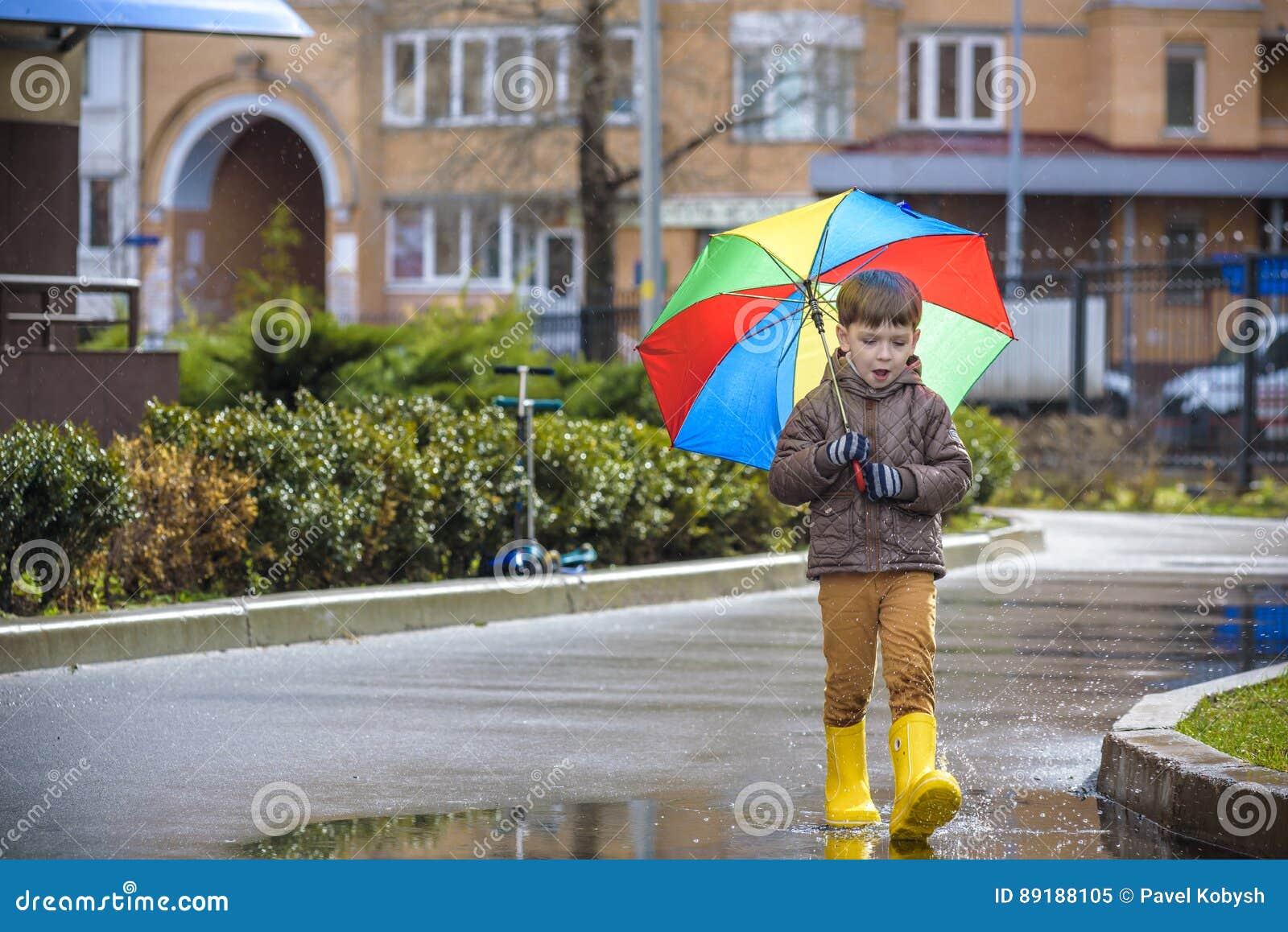 Ragazzino che gioca nel parco piovoso di estate Il bambino con l ombrello variopinto dell arcobaleno, impermeabilizza il cappotto