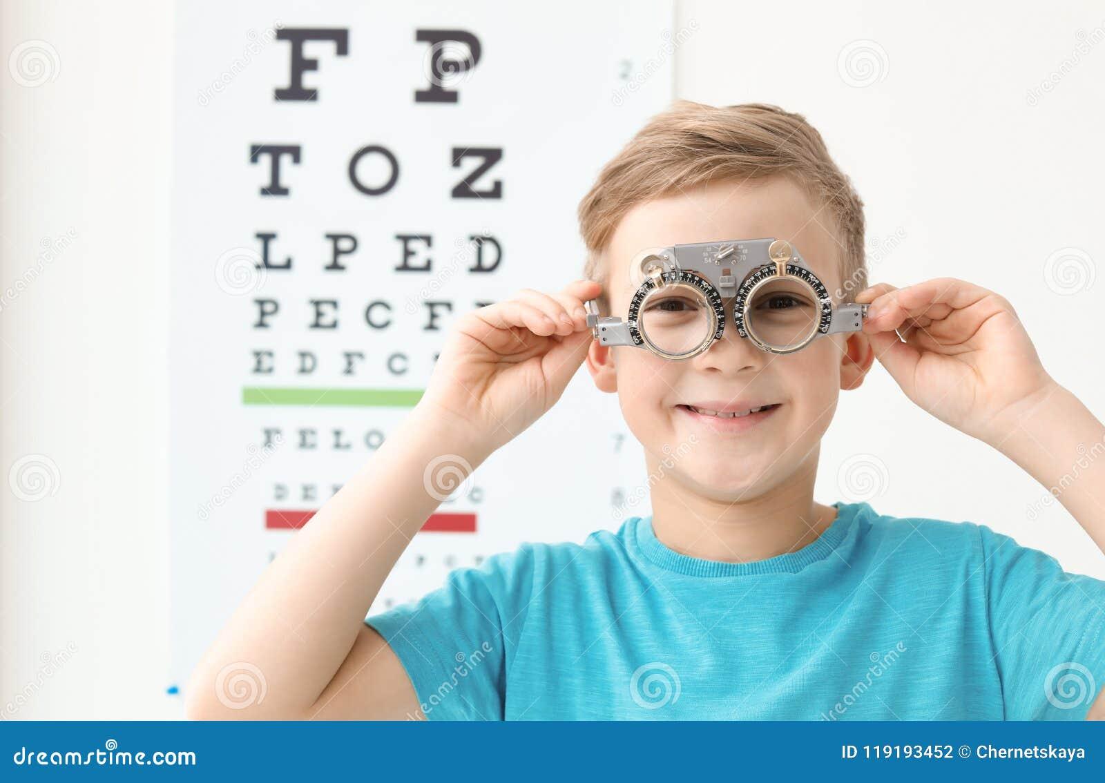 Ragazzino con la struttura di prova vicino al grafico di occhio