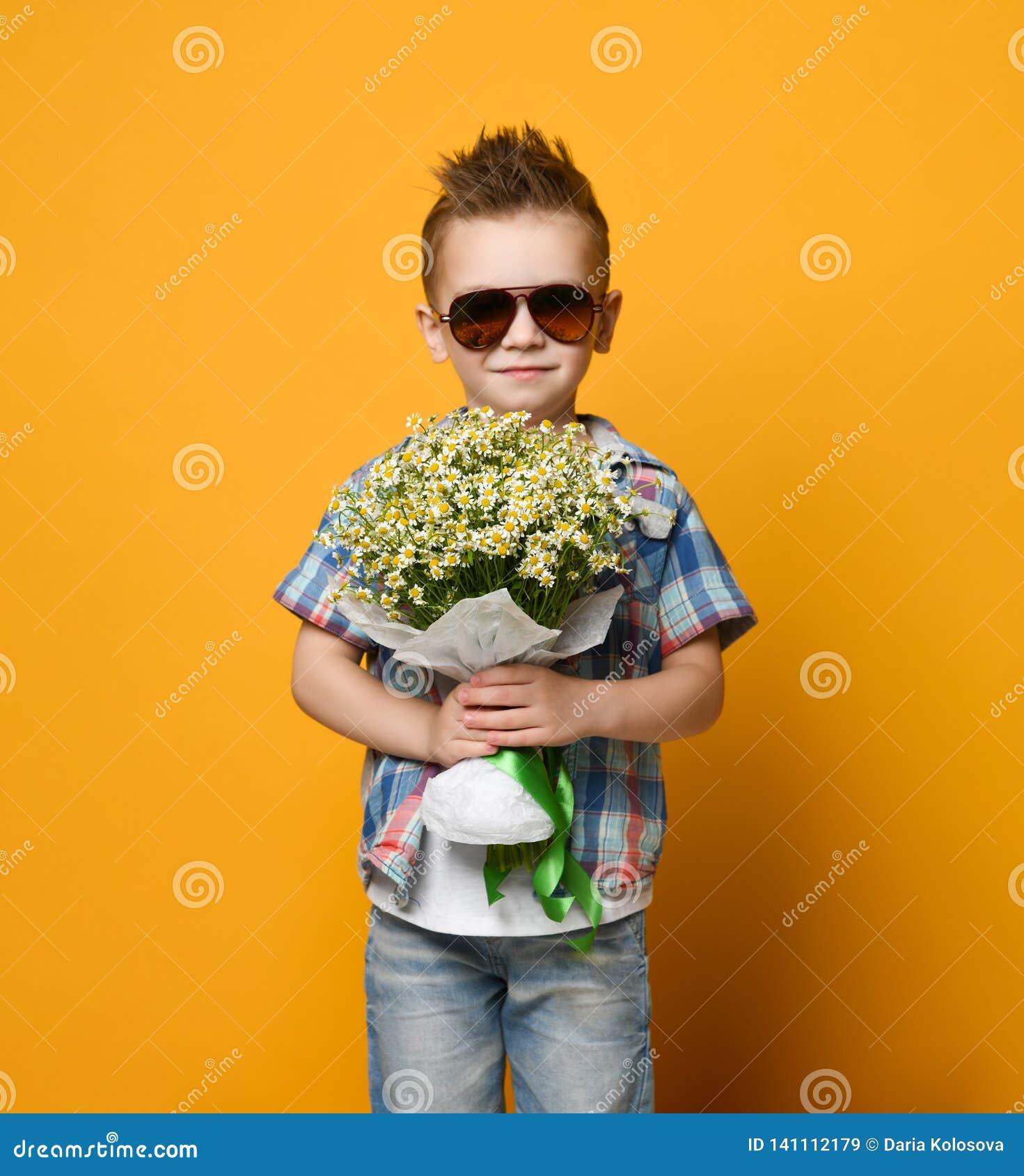 Ragazzino sveglio che tiene un mazzo dei fiori