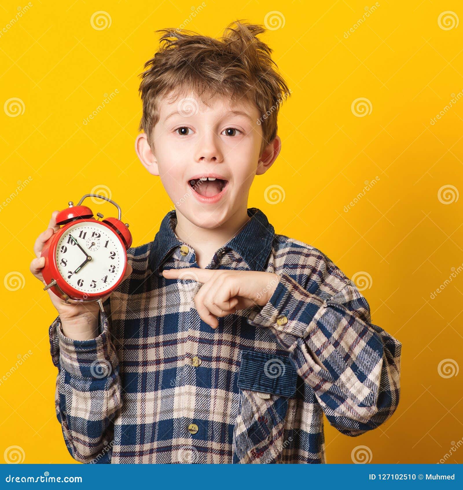 Ragazzino sveglio con la sveglia, isolata su giallo Bambino divertente che indica alla sveglia a 7 in punto alla mattina Eccedenz