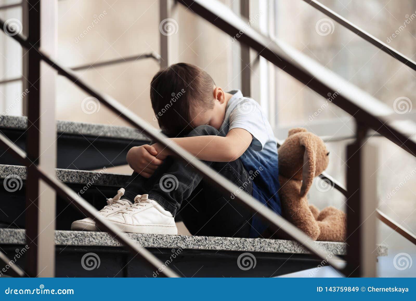 Ragazzino triste con il giocattolo che si siede sulle scale