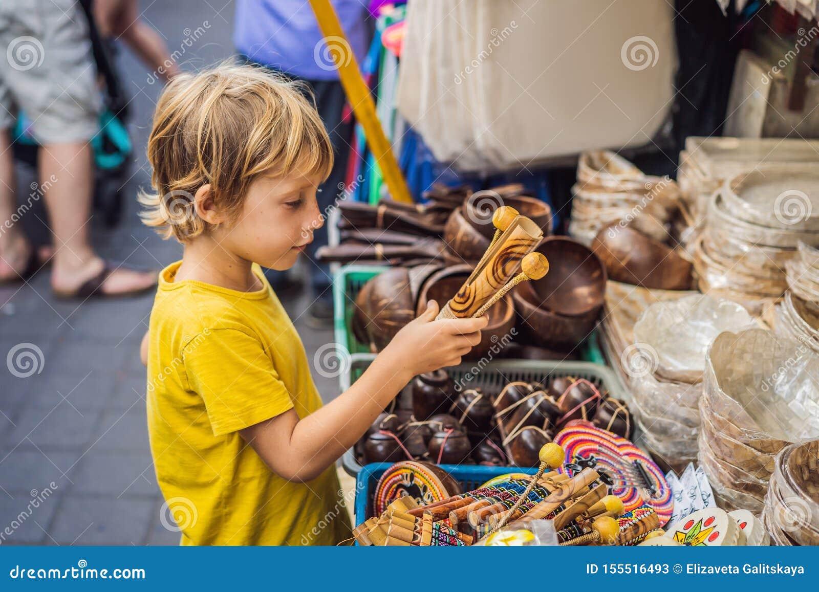Ragazzo ad un mercato in Ubud, Bali Negozio di ricordo tipico che vende i ricordi e gli artigianato di Bali al mercato famoso di
