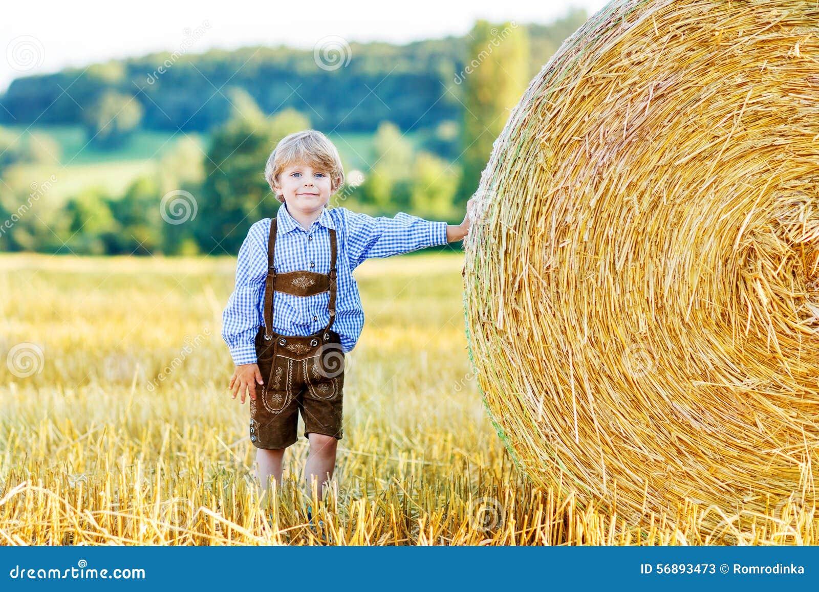 Ragazzo adorabile del bambino divertendosi con la pila del fieno sul giacimento di grano