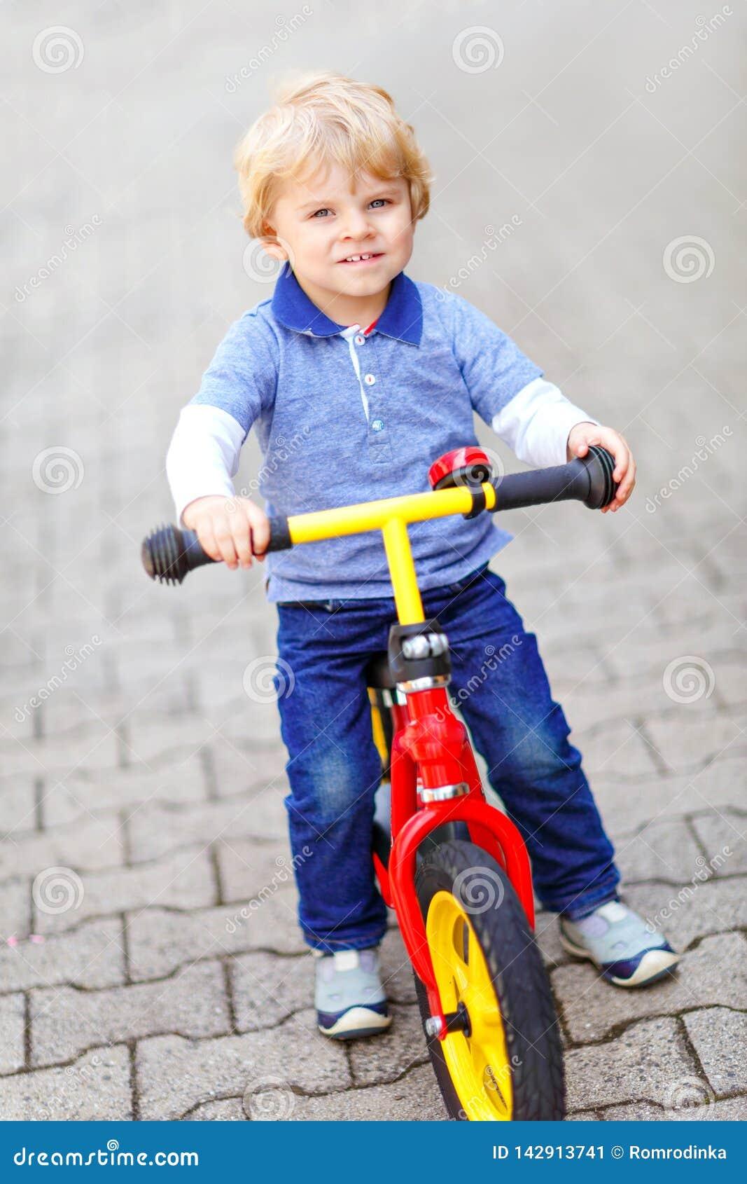 Ragazzo biondo attivo del bambino in vestiti variopinti che determinano equilibrio e la bici o la bicicletta del principiante in