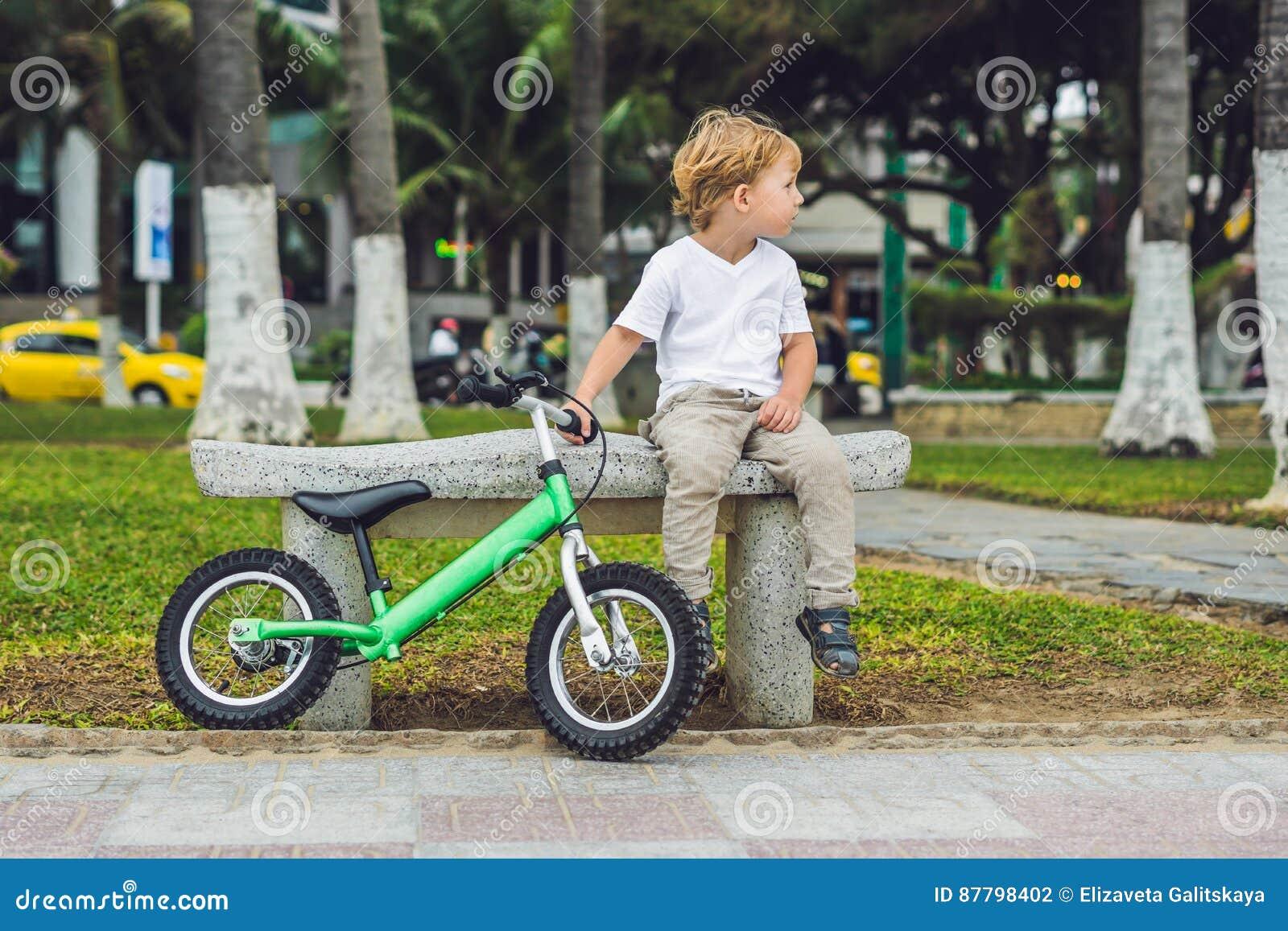 Ragazzo Biondo Attivo E Bicicletta Del Bambino Vicino Al Mare