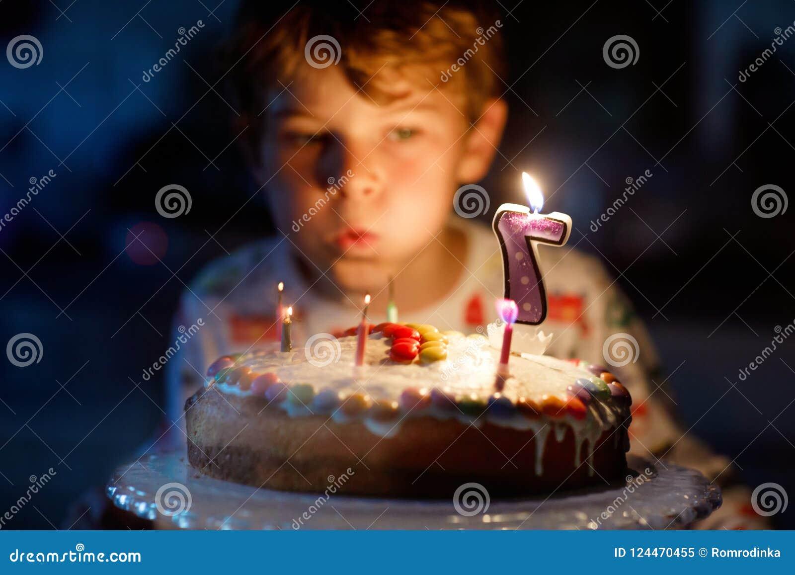 Ragazzo biondo felice del bambino che celebra il suo compleanno Bambino che soffia sette candele sul dolce al forno casalingo, de