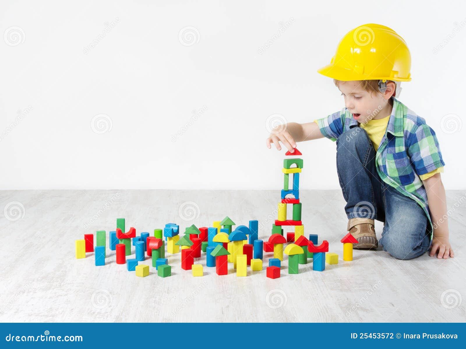 Ragazzo in cappello duro che gioca con i blocchi