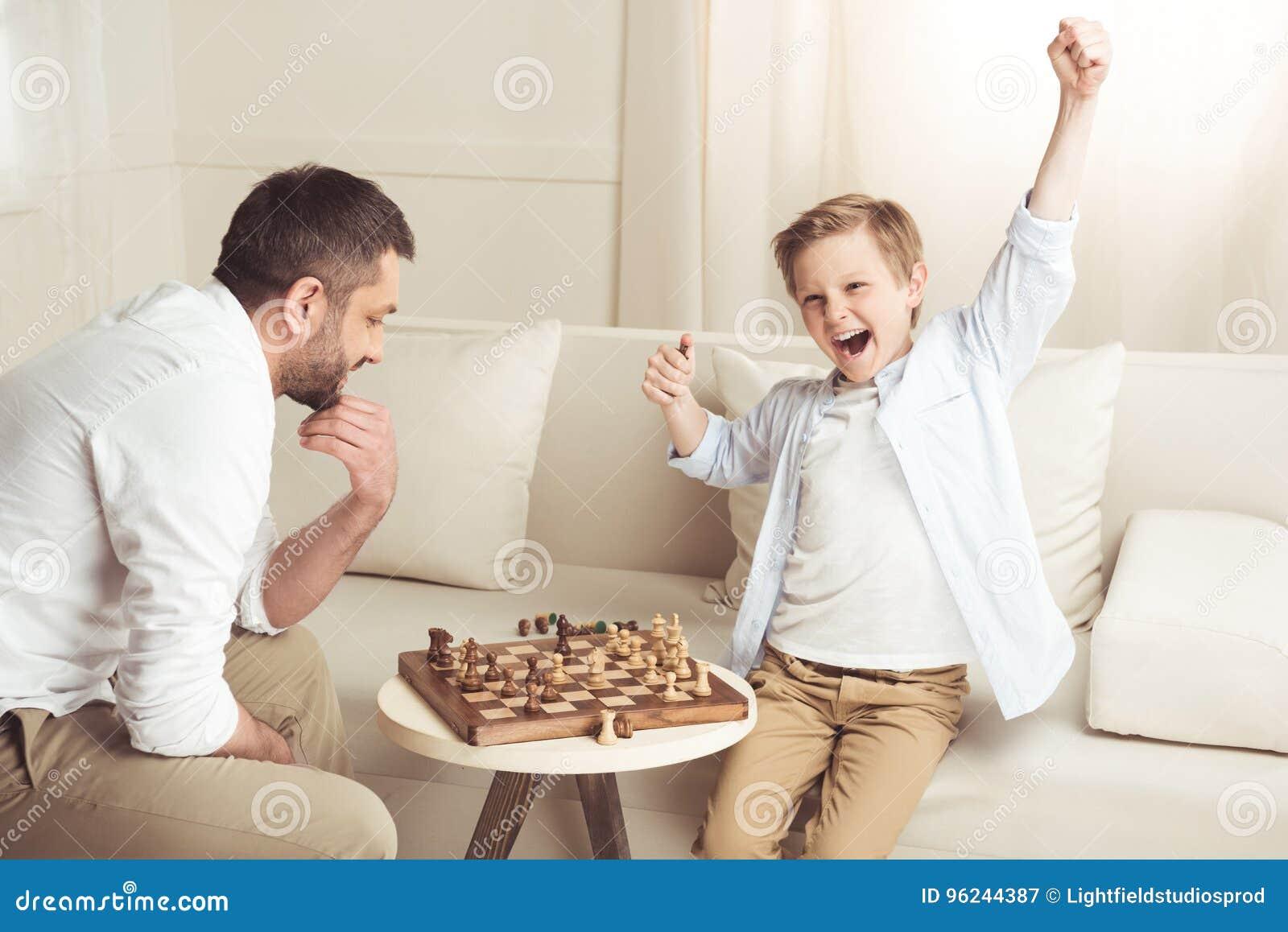 Ragazzo che celebra successo nel gioco di scacchi con il padre vicino vicino