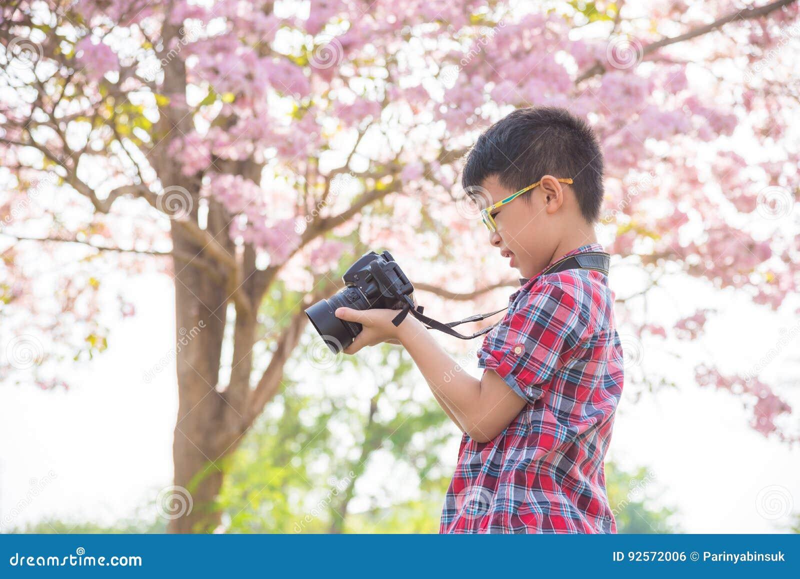 Ragazzo che controlla foto in camera al parco