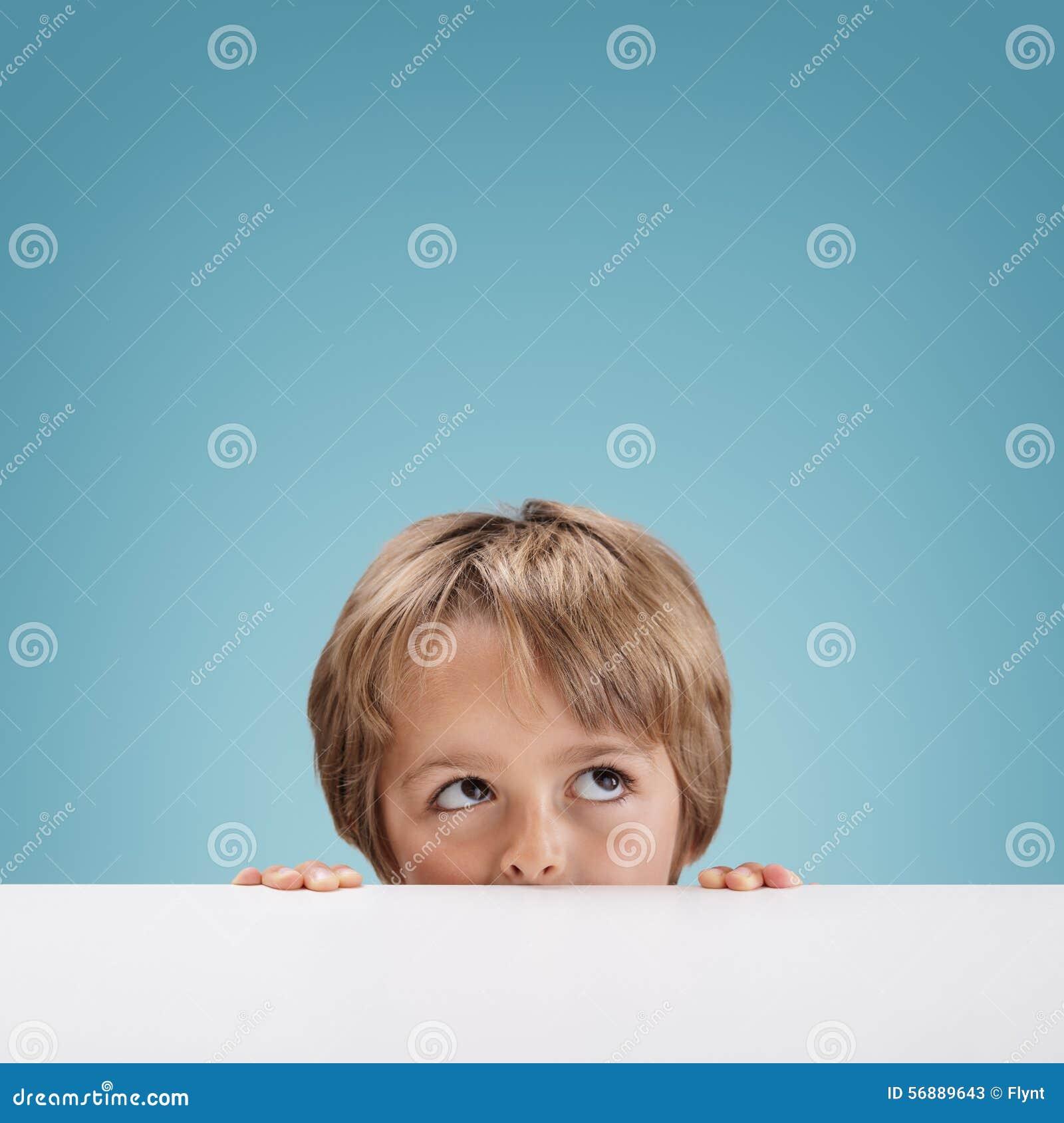 Ragazzo che dà una occhiata sopra un bordo bianco