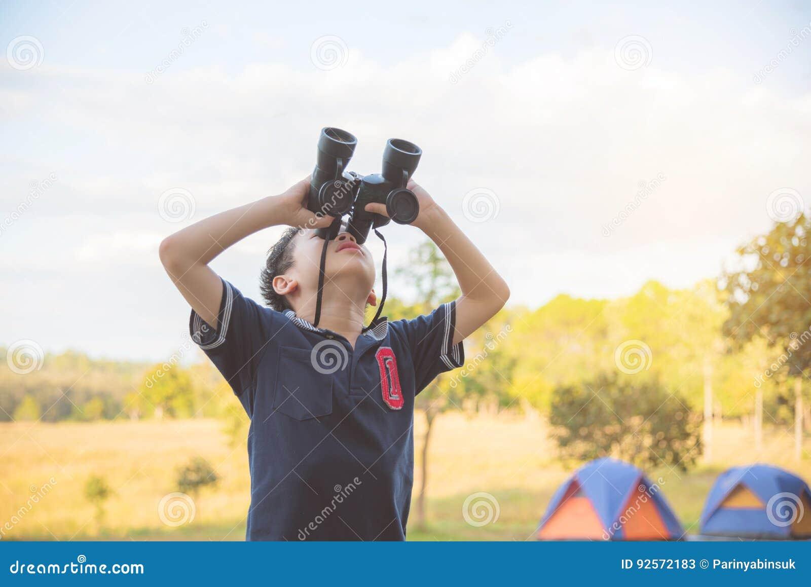 Ragazzo che esamina dal binocolo il campeggio