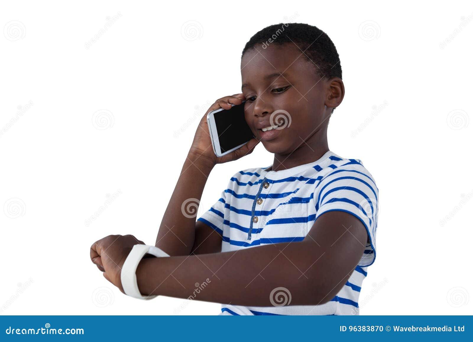 Ragazzo che esamina il suo orologio astuto mentre parlando sul telefono cellulare