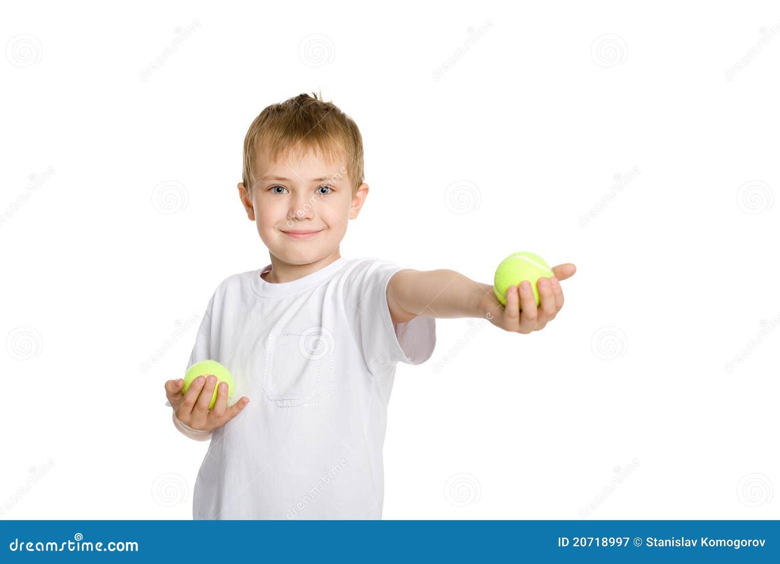 Ragazzo che gioca nelle sfere di tennis.