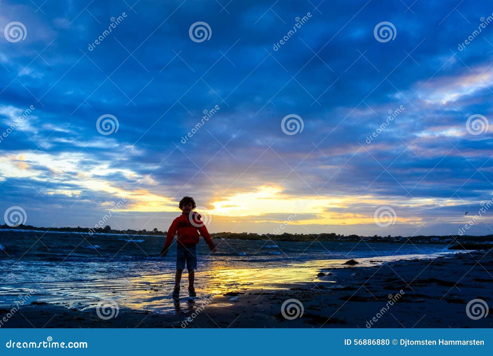 Ragazzo che gioca sulla spiaggia al tramonto
