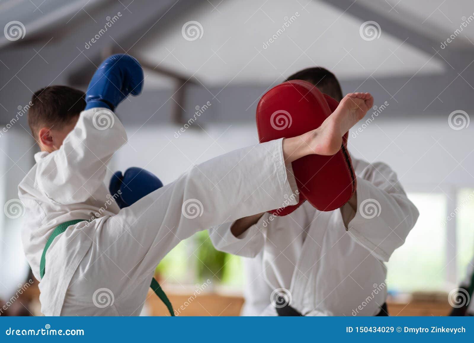 Ragazzo che indossa i guanti protettivi blu che hanno lotta con l istruttore