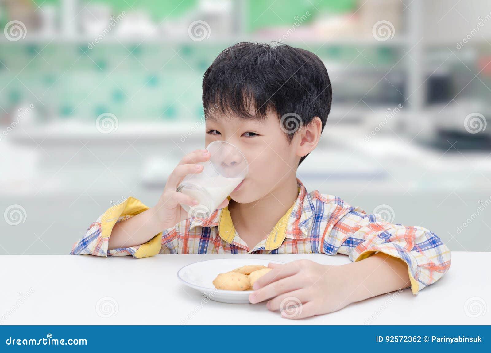 Ragazzo che mangia i biscotti con latte in cucina