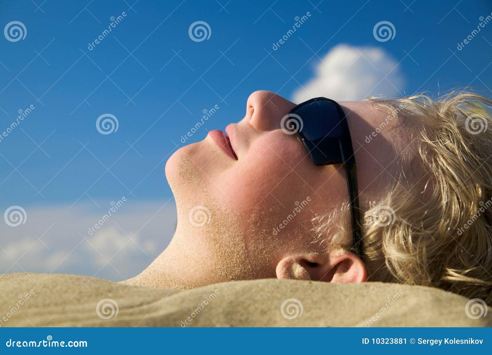 Ragazzo che si distende sulla spiaggia di estate in occhiali da sole