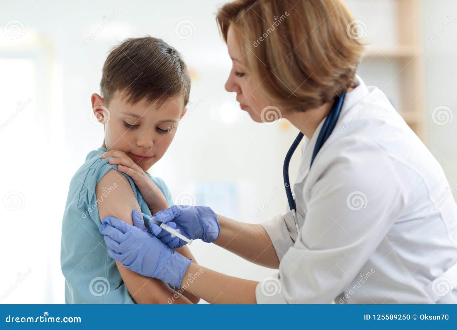 Ragazzo coraggioso che riceve iniezione o vaccino con un sorriso