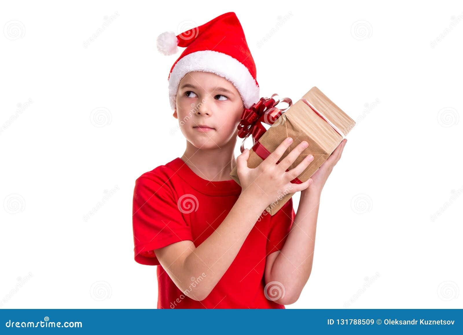 Ragazzo curioso bello, cappello di Santa sulla sua testa, controllante il contenitore di regalo Concetto: natale o festa del buon