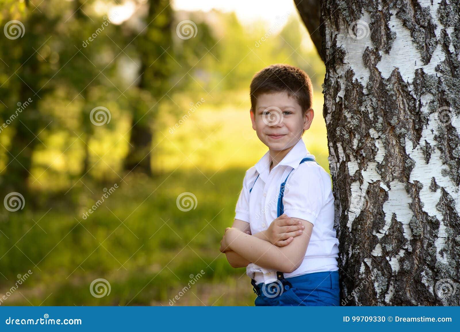 Ragazzo del ritratto che sta vicino all albero in parco, piegato le sue mani davanti lui