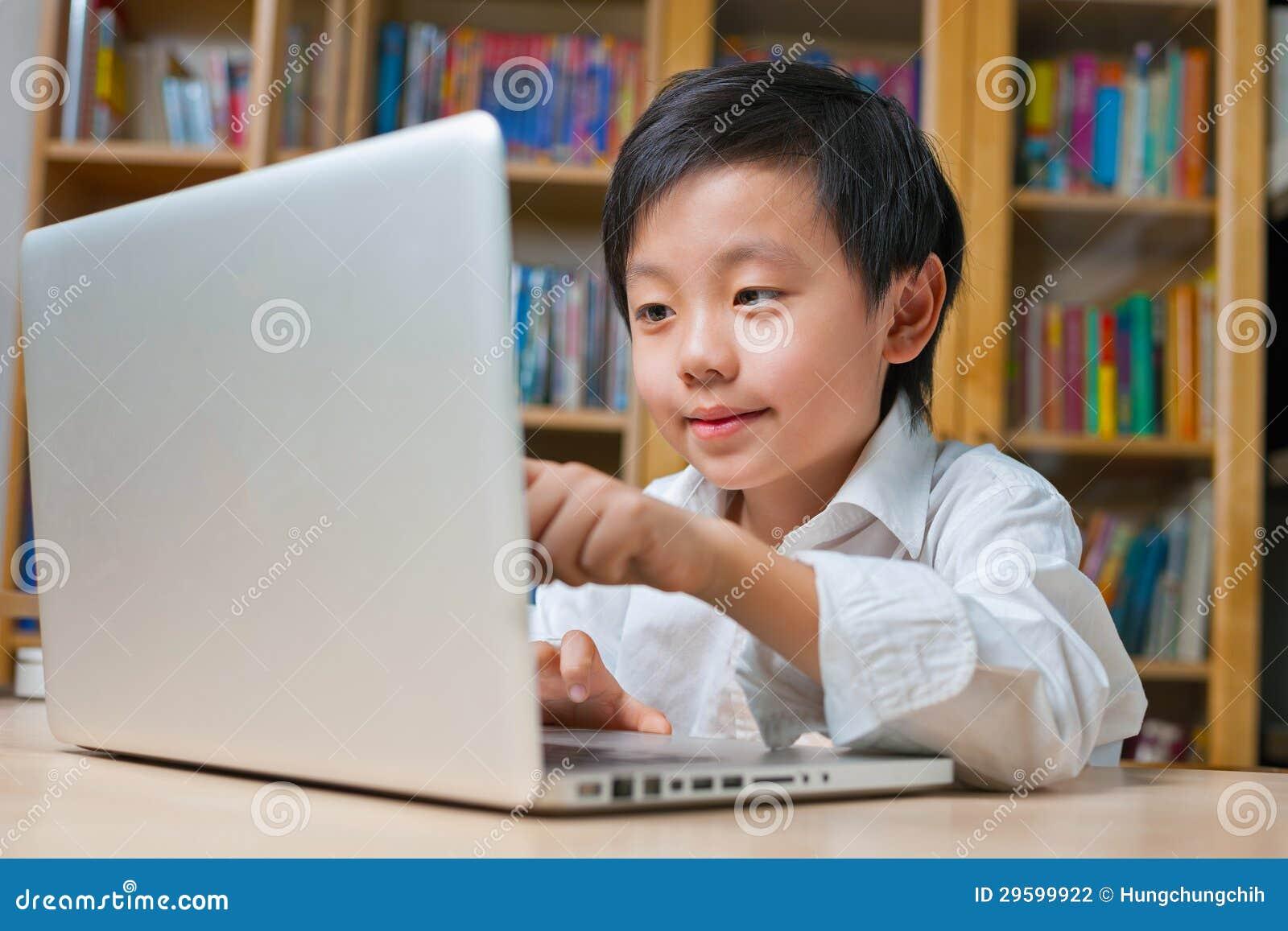 Ragazzo di banco in camicia bianca davanti al computer portatile