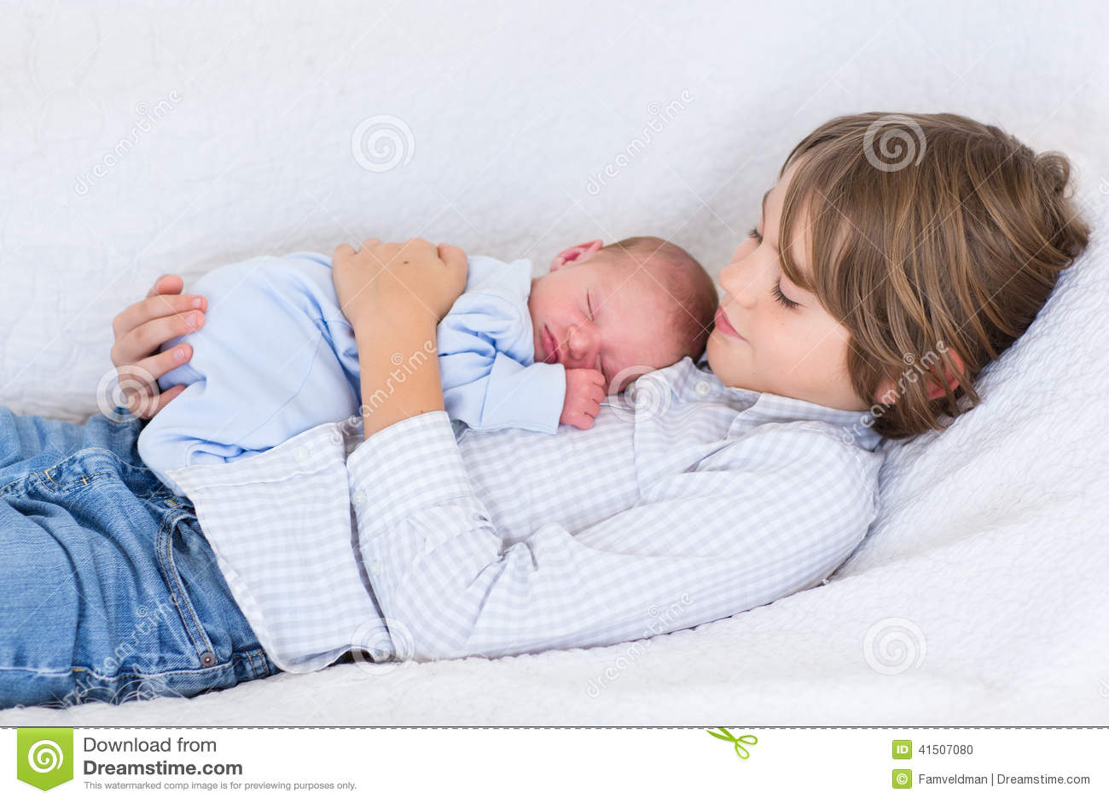 Ragazzo di neonato che dorme nelle armi di suo fratello