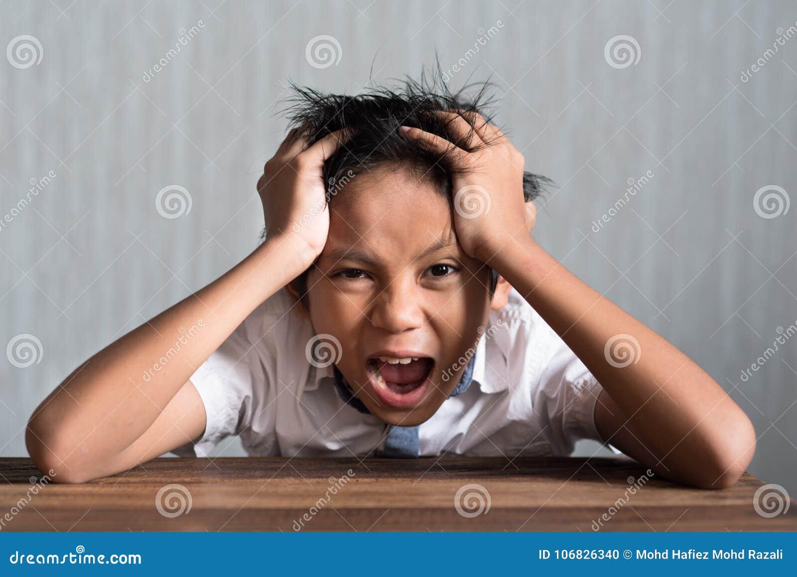 Ragazzo di scuola asiatico che tiene la sua testa sulla tavola di legno che ritiene così sforzo