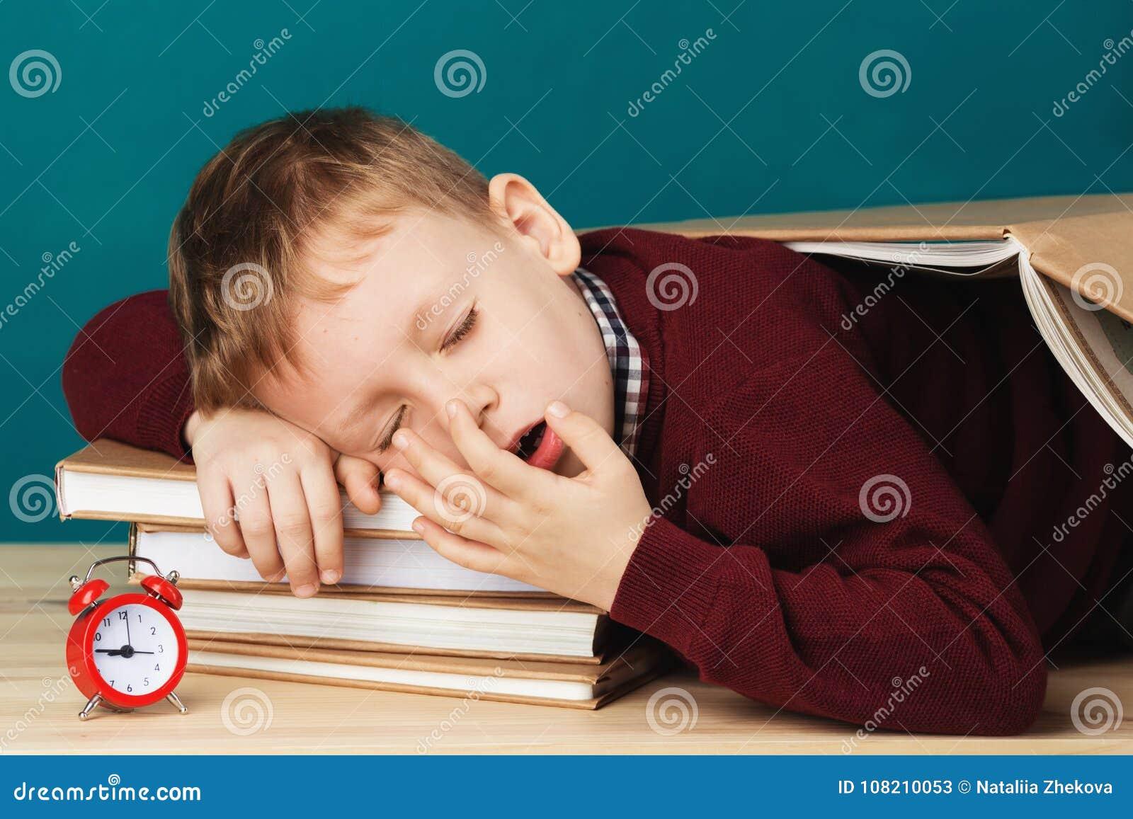 Ragazzo di scuola stanco addormentato sui libri piccolo studente che dorme sul tex