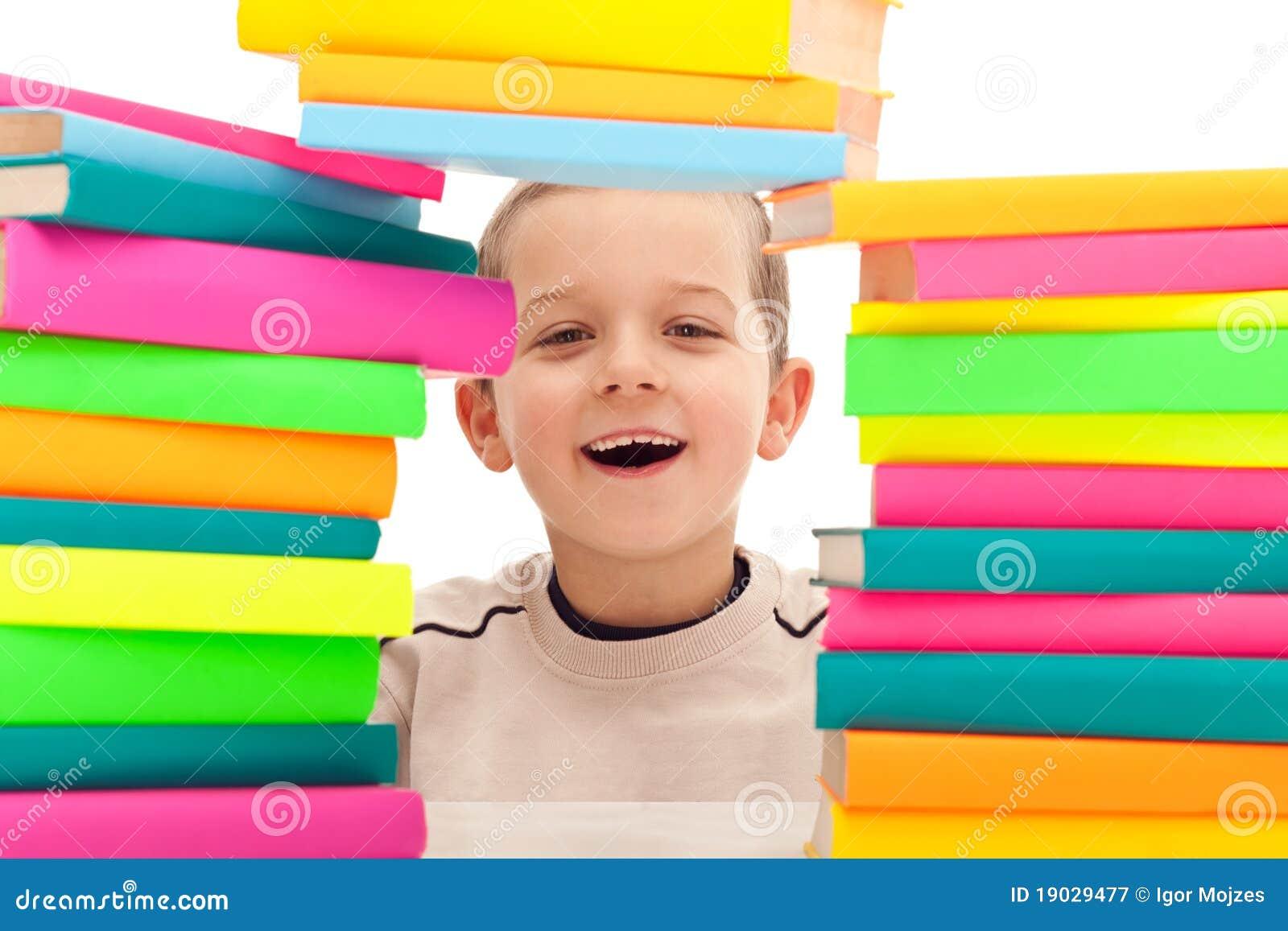 Ragazzo dietro il mucchio dei libri