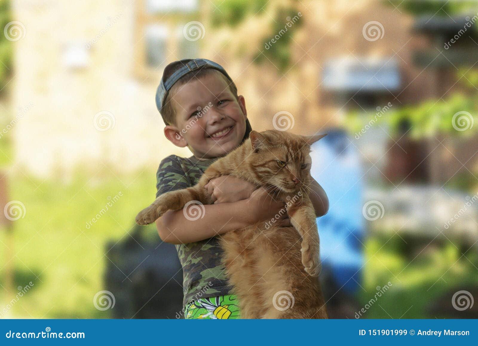 Ragazzo divertente che abbraccia un gatto con i lotti di amore Ritratto del bambino che tiene sulle mani un grande gatto Giocando