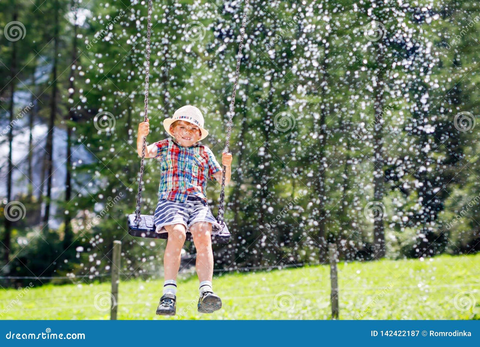 Ragazzo divertente del bambino divertendosi con l oscillazione a catena sul campo da giuoco all aperto mentre essendo bagnato spr