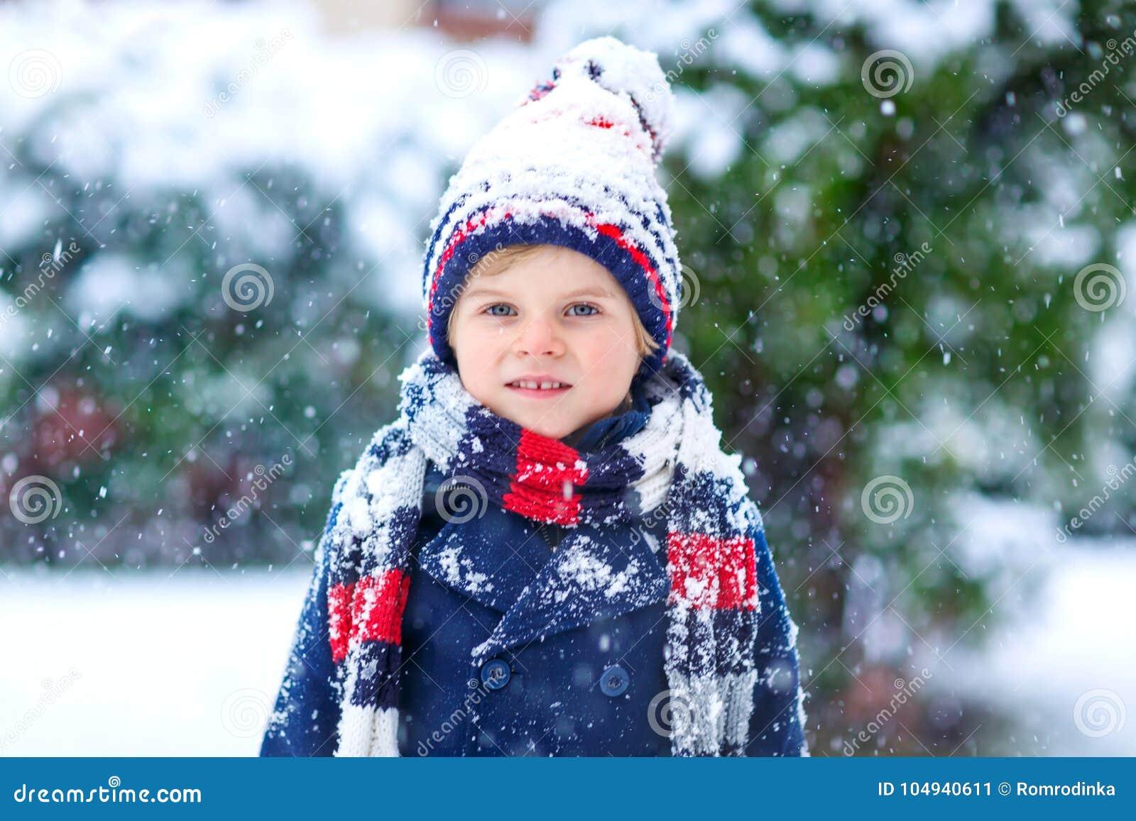Ragazzo divertente del bambino in vestiti variopinti che giocano all aperto durante le forti precipitazioni nevose